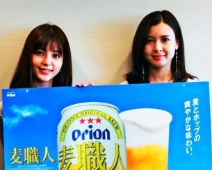 新たな製法で生まれ変わった「麦職人」をPRする南里美希さん(左)、奥間唯さん=7日、沖縄タイムス社