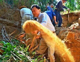 スコップで土をかき出す鳩山由紀夫元首相=宜野座村祖慶