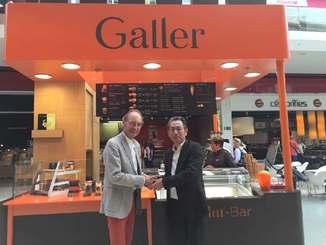 ガレーの創始者ジャン・ガレー氏(左)と握手するGRIの糸数剛一社長=8月28日、ベルギーのガレー店舗(GRI提供)