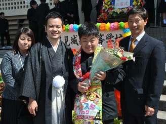 東江祐飛さん(右から2人目)を祝福する西村松太朗教諭(同3人目)と母紀美さん、父誠治さん=1日、県立豊見城南高校