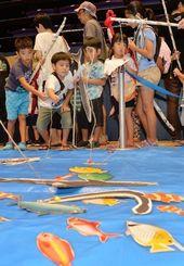 釣り堀コーナーで大物を釣り上げる子どもたち=9日午前、那覇市久茂地・タイムスホール