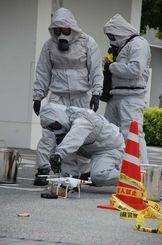 訓練で小型無人機「ドローン」に付けられている危険物の回収を試みる機動隊員=8日、那覇市県立博物館・美術館