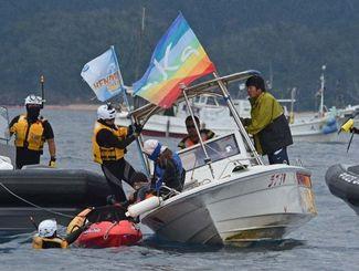 臨時制限水域付近で、抗議船(中央)に乗り移りながらカヌーを確保する海上保安官=11日午前11時ごろ、名護市辺野古沖