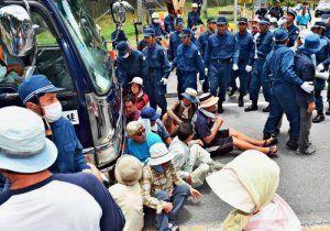 基地内に入る工事関係車両を阻止しようと座り込む住民ら=11日午後0時19分、東村高江・米軍北部訓練場メインゲート前