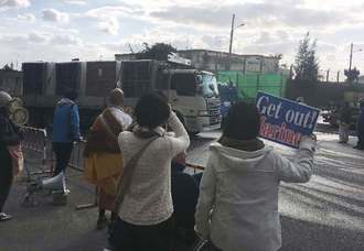 工事資材を運ぶ車両に向け抗議のプラカードを掲げる市民ら=13日、名護市辺野古の米軍キャンプ・シュワブゲート前