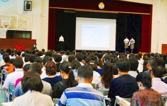 開邦中学の説明に熱心に聞き入る参加者ら=13日、南風原町・開邦高校