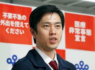 大阪府庁で取材に応じる吉村洋文知事=23日午後4時38分