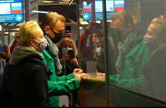17日、モスクワの空港で入国審査場に立つナワリヌイ氏(中央)と妻。ナワリヌイ氏はこの後、拘束された(AP=共同)