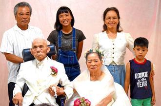 新郎・新婦の衣装に身を包んだ又吉真行さん(前列左)ヒデさん(同右)夫妻と家族=中城村添石・介護老人保健施設「信成苑」