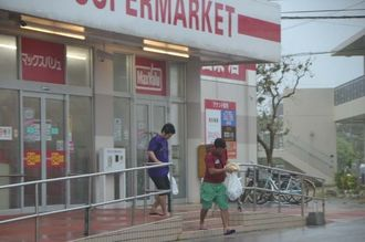 強風に煽られ、体をかがめてスーパーを出る男性23日午後5時すぎ、石垣市登野城
