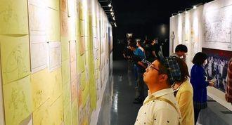 「エヴァンゲリオン展」で展示された原画やセル画に見入る来場者=6日午後、那覇市おもろまちの県立博物館・美術館