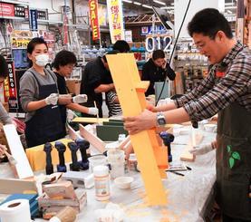 店員の助言を受けながら塗装する参加者ら=18日、浦添市・メイクマン浦添本店