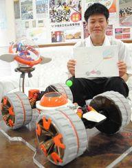 車体と運転席が離れた斬新なデザインの原画を手に、受賞を喜ぶ平良魁斗君と、贈られた模型=17日、北山高校