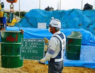 DDTや油で汚染された土壌を詰めたドラム缶をトラックに積み込む作業員=8日、沖縄市諸見里
