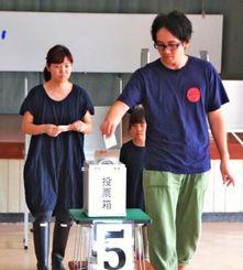 竹富町役場の建設位置をめぐる住民投票で、一票を投じる親子連れ=小浜公民館