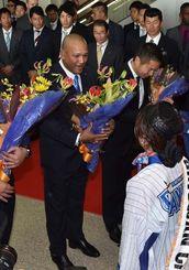 歓迎セレモニーで花束を受け取るにDeNAのアレックス・ラミレス監督(左)ら=31日午後、那覇空港