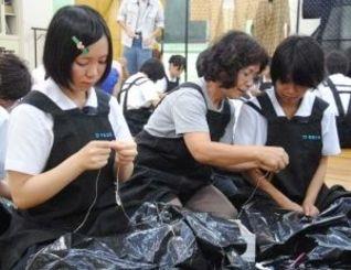 喜如嘉芭蕉布の織り手(中央)の指導を受けながら、苧績みに取り組む生徒たち=11日、首里高校