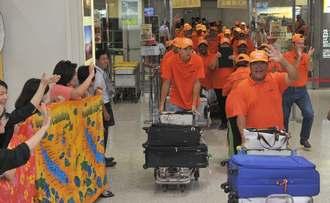 大きな拍手で出迎えられたニューカレドニアからの参加者=20日午後、那覇空港