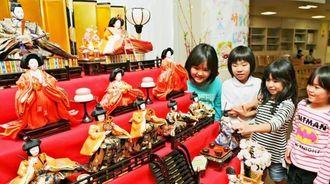 「一番上の男の人の名前何だっけ」などと言いながら、ひな人形を興味深そうに眺める児童たち=2日午後、那覇市・金城児童館