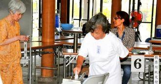 繰り上げ投票で1票を投じる竹富島の有権者ら=9日、竹富町・竹富島まちなみ館