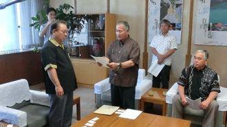 名護市議会の屋比久稔議長(中央)がUSJの誘致に支援を求める意見書を、安慶田光男副知事(左)に手渡した=県庁