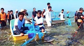 晴天の下、小船に乗って網を狭め、魚を追い込む子どもたち=久高島・ピザ浜