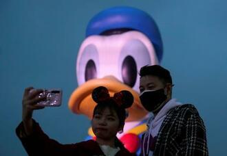 24日、中国の上海ディズニーランド付近で自撮りをする訪問客(ロイター=共同)
