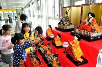 駅のコンコースでひな人形を飾る子どもたち=26日午後、那覇市のゆいレール小禄駅(伊藤桃子撮影)