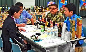 フェアに向けた商談会で商品をPRする参加者ら=7日、那覇市・沖縄産業支援センター