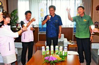 県産牛乳をグラスに注ぎ、消費拡大を期して乾杯する新里菊也会長(左から2人目)、高良倉吉副知事(同3人目)ら=5日、県庁