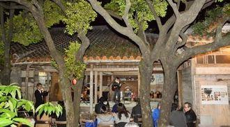 大きなクロキのある庭と母屋を舞台に開かれた名護ナイト=22日、名護市大中