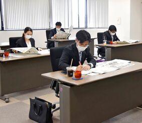 新聞を読み込む新入社員=9日、浦添市・琉球セメント本社