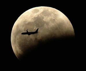 下側から欠け始めた月=4日午後7時45分、那覇市久茂地から(絞り11、200分の1秒露光、伊藤桃子撮影)