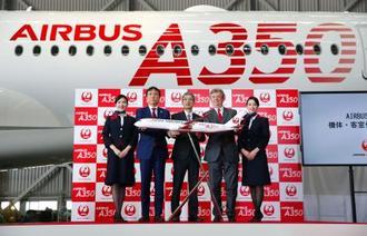 エアバスA350の初号機の前で写真に納まる日本航空の赤坂祐二社長(中央)ら=20日午前、羽田空港