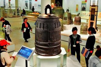 打音も聞くことができるようになった「万国津梁の鐘」(中央)。後方にも15世紀の鐘が並ぶ=24日、那覇市おもろまちの県立博物館・美術館