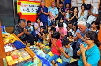 ウークイで、仏壇に向かい手を合わせる上原武さん(左)と親族=25日午後、糸満市糸満(下地広也撮影)