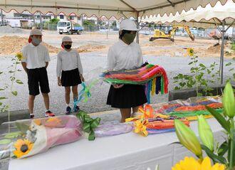 米軍機墜落事故の犠牲者の冥福を祈り、花と千羽鶴を供える宮森小学校の児童=30日午前、うるま市・同校
