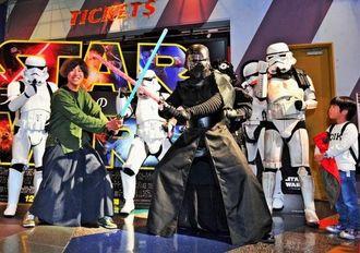 映画に登場するキャラクターにふんし、記念撮影するスター・ウォーズファン=18日午後、那覇市おもろまち・シネマQ