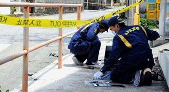 被害者のものとみられる血痕などを調べる県警の捜査員=久米島町鳥島(比嘉正明通信員撮影)