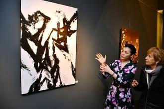 個展会場で作品を説明する中塚翠涛さん(左)=14日、パリ(共同)