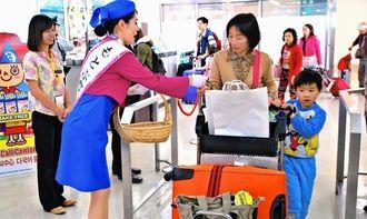 もとぶミス桜から星砂を受け取る台湾人観光客=那覇空港国際線ターミナル