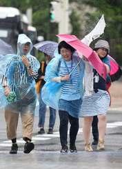 横殴りの強い風雨にあおられる歩行者=15日午後3時ごろ、那覇市久茂地(国吉聡志撮影)