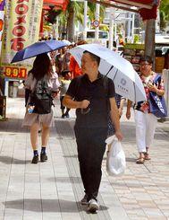 国際通りで日傘を差して歩く男性。紫外線対策で愛用する人が増えている=那覇市久茂地