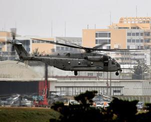 普天間飛行場を離陸するCH53E大型輸送ヘリ。後方の建物は沖国大=9日午後2時すぎ、宜野湾市(渡辺奈々撮影)