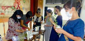 花谷友子さん(左)から植物ヘナを使ったペーストの作り方を学ぶ主婦ら=9月20日、石垣市・平得公民館