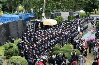 29日、タイの首都バンコクの陸軍第11歩兵連隊基地前で、警備に当たる警官隊(共同)