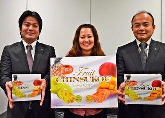 新商品「フルーツちんすこう果肉入りマンゴー&パイン」をPRする南都物産の松堂保部長(右)ら=3日、沖縄タイムス社