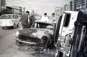 焼き打ちにされた米人車両の状況を確認する警察関係者とみられる人たち=1970年12月20日、沖縄市