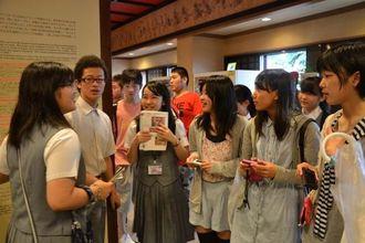 興南中学校の生徒の説明を聞く中辺路中学校の生徒ら(右の3人)=首里城公園