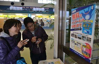 無料WiFiへの接続やアプリを試す旅行者=2014年、石垣港離島ターミナル